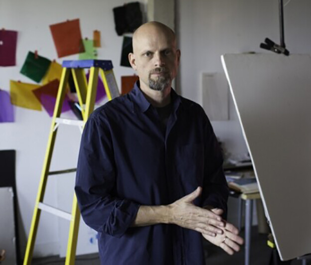 Photo of Brent Wahl with ladders and color block wall art behind him